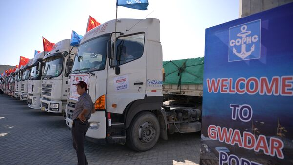 A Chinese worker stands near trucks carrying goods during the opening of a trade project in Gwadar port, some 700 kms west of the Pakistani city of Karachi on November 13, 2016. - Sputnik International