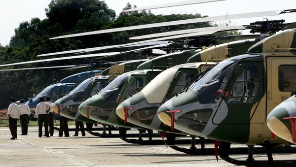 Officials walk past a line of parked Dhruv helicopters of India's Hindustan Aeronautics Ltd. (HAL) standing on the tarmac at The HAL helicopter division in Bangalore - Sputnik International
