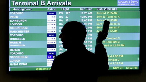 A person points to a screen with an airplane travel list while holding up a phone at Newark Liberty International Airport, in Newark, N.J. - Sputnik International