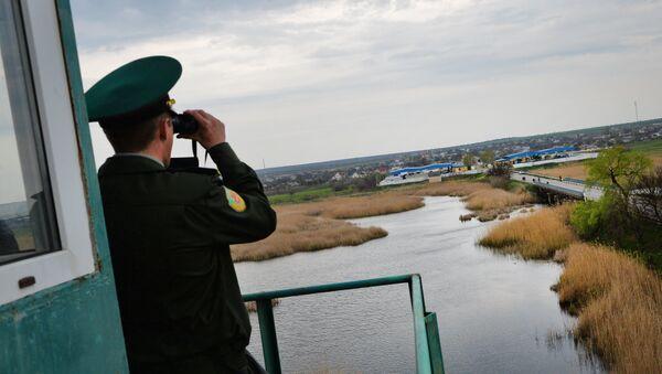 A transdniestr border police officer from separatist region of Moldova looks at Ukraine border point at Kuchurgan-Pervomaysk, Ukraine-Moldova border point on April 15, 2014. - Sputnik International