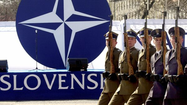 Members of a honour guard present arms in front of the NATO logo during a ceremony to mark the country's entry into the military alliance on Friday, 2 April 2004 in Bratislava - Sputnik International