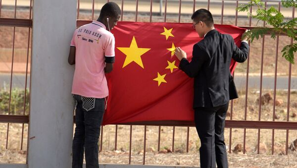 A Senegalese worker and a Chinese man put a Chinese flag in Diamniadio district in Dakar on May 7, 2017 during the visit of Chinese vice president Li Yuanchao (not seen) - Sputnik International