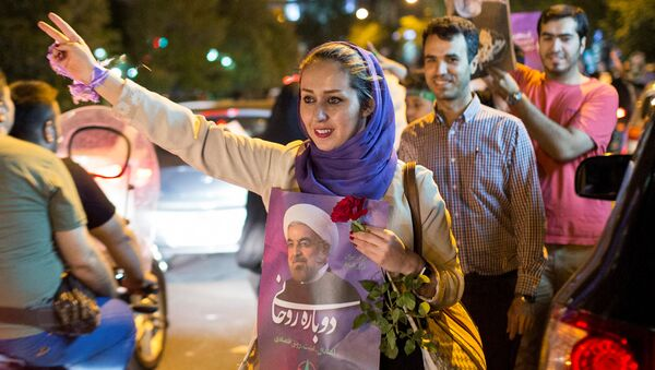 A woman holds a poster of Iranian President Hassan Rouhani during a campaign rally in Tehran, Iran, May 17, 2017 - Sputnik International