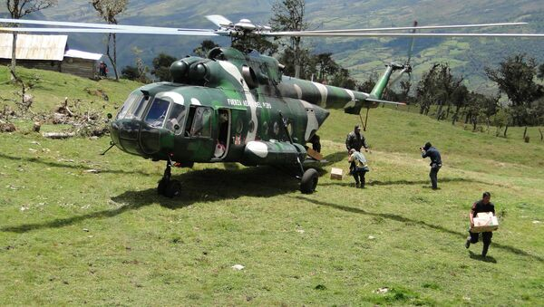 A rescue worker unloads supplies from a Peruvian Air Force helicopter at a camp set up near the cave where an injured Spanish speleologist remains trapped, in Leimebamba, Peru, Friday, Sept. 26, 2014 - Sputnik International