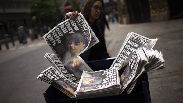 A woman picks a newspaper reporting the news on the suicide attack at a concert by Ariana Grande that killed more than 20 people as it ended Monday night in central Manchester, Britain, Wednesday, May 24, 2017. - Sputnik International