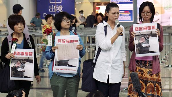 Li Ching-yu, center right, wife of Taiwanese pro-democracy activist Li Ming-che detained in China, gives a press conference after she was denied boarding the flight to Beijing at the airport counter at Taoyuan international airport in Taoyuan, Taiwan Monday, April 10, 2017. - Sputnik International