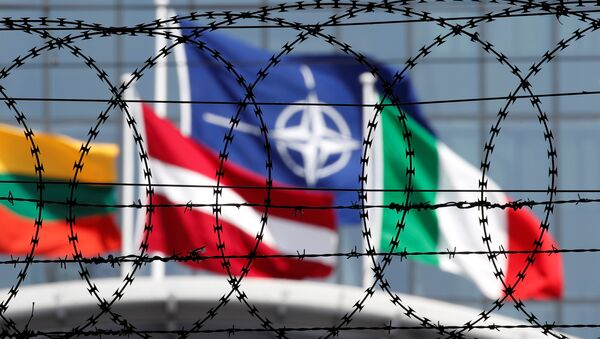 The NATO flag is seen through barbed wire as it flies in front of the new NATO Headquarters in Brussels, Belgium May 24, 2017 - Sputnik International
