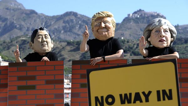 Protesters wear masks depicting the leaders of the G7 countries during a demonstration organised by Oxfam in Giardini Naxos near Taormina, Sicily, Italy, May 27, 2017 - Sputnik International
