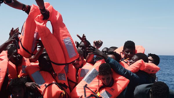 Migrants in an overcrowded plastic raft reach out for life jackets during a search and rescue operation by rescue ship Aquarius, operated by SOS Mediterranean and Doctors without Borders, in central Mediterranean Sea May 18, 2017 - Sputnik International