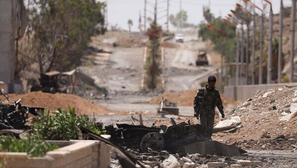 A Syrian Democratic Forces (SDF) fighter walks through a damaged street in the Syrian city of Tabqa, after SDF captured it from Daesh militants, May 12, 2017 - Sputnik International