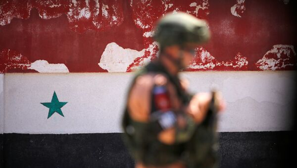 A Russian soldier stands guard near a Syrian national flag drawn on the wall as rebel fighters and their families evacuate the besieged Waer district in the central Syrian city of Homs, after an agreement reached between rebels and Syria's army, Syria May 21, 2017 - Sputnik International