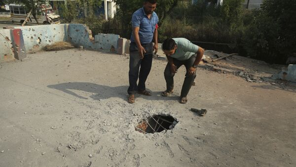Indian civilians inspect the rooftop of a house damaged by mortar shells allegedly fired from the Pakistan side of the border, at a residential area near the Line of Control at the India Pakistan border at Jhanghar village, in Nowshera, India, Sunday, May 14,2017 - Sputnik International