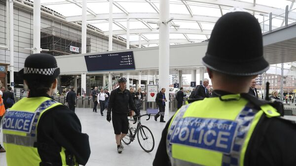 Police watch as commuters pass through Manchester Victoria railway station in Manchester England, which has reopened for the first time since the terror attack on the adjacent Manchester Arena Tuesday May 30, 2017 - Sputnik International
