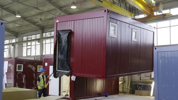 Worker moves a modular container - Sputnik International