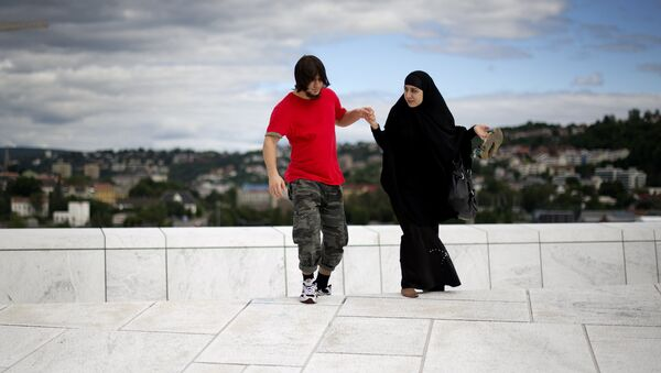 A man helps a woman up a step on the roof of the Opera house in Oslo - Sputnik International