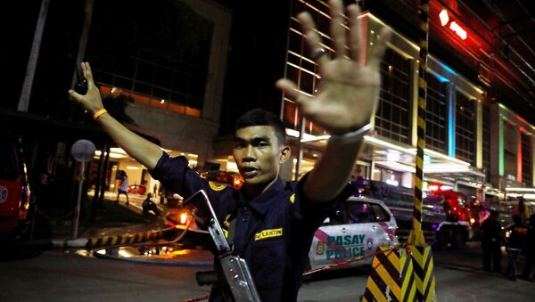 A security guard stops photographers from entering the vicinity of Resorts World Manila after gunshots and explosions were heard in Pasay City, Metro Manila, Philippines June 2, 2017. - Sputnik International
