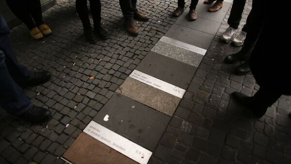 In this photo taken Sunday, Oct. 9, 2016 people stand around the public art piece 'Meinstein' (My Stone), by Nadia Kaabi-Linke, which shows the percentage of migrants in the district of Neukoelln with different stones, during a so called 'Refugee Tour' by Syrian refugee Firas Zakri trough Neukoelln in Berlin, Germany - Sputnik International