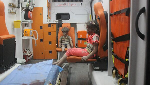 5-year-old Omran Daqneesh and his sister sit in an ambulance after being pulled out of a building hit by an airstrike in Aleppo, Syria, on Aug. 17, 2016 - Sputnik International
