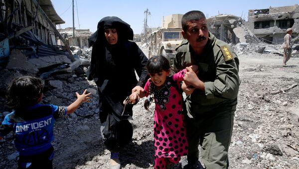 Iraqi soldiers help residents displaced by fighting between Iraqi forces and Islamic State militants in Mosul's al-Zanjili's district, Iraq June 7, 2017. - Sputnik International
