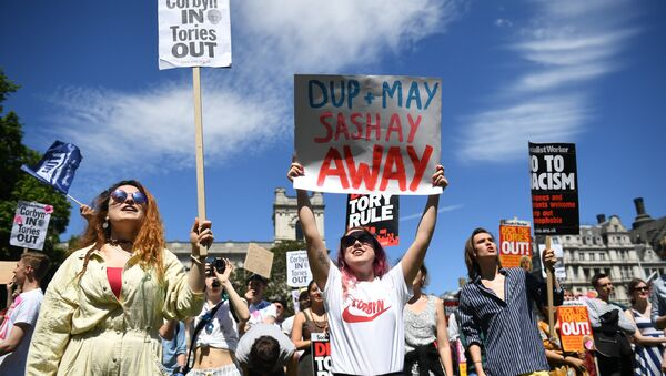 Anti-Conservative Party and anti-Democratic Unionist Party (DUP) demonstrators gather with placards in Parliament Square in front of the Houses of Parliament in central London on June 10, 2017 - Sputnik International