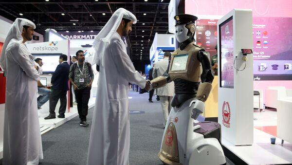 A visitor shakes hands with an operational robot policeman at the opening of the 4th Gulf Information Security Expo and Conference (GISEC) in Dubai, United Arab Emirates, May 22, 2017. Picture taken May 22, 2017 - Sputnik International