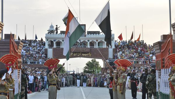 In this July 21, 2015 file photo, Indian and Pakistani flags are lowered during a daily retreat ceremony at the India-Pakistan joint border check post of Attari-Wagah near Amritsar, India - Sputnik International