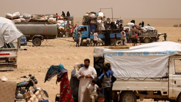 Internally displaced people who fled Raqqa city gather near vehicles carrying their belongings in a camp near Ain Issa, Raqqa Governorate, Syria May 19, 2017 - Sputnik International