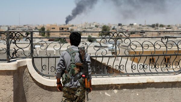 A Kurdish fighter from the People's Protection Units (YPG) looks at a smoke after an coalition airstrike in Raqqa, Syria June 16, 2017 - Sputnik International