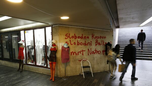 People pass through an underground passage with graffiti on the wall that reads: Free Kosovo, Free Balkan, Death for NATO, in Belgrade, Serbia (File) - Sputnik International