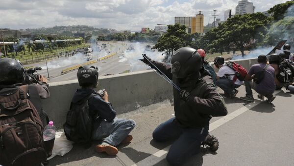 An anti-government demonstrator aims a slingshot during clashes with security forces along a highway in Caracas, Venezuela, Monday, June 19, 2017 - Sputnik International