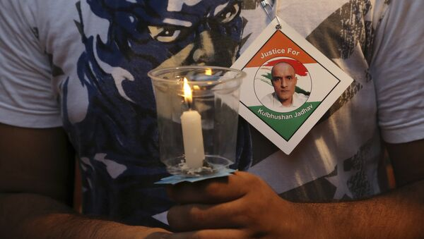 An Indian man holds a candle as he participates in a demonstration in support of Indian naval officer Kulbhushan Jadhav in Mumbai, India, Saturday, June 03, 2017 - Sputnik International