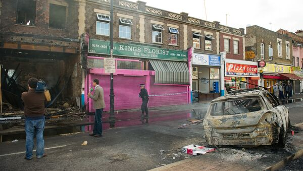 A police officer sets up a cordon around a burnt-out shop on High Road in Tottenham, north London on August 7, 2011.  - Sputnik International