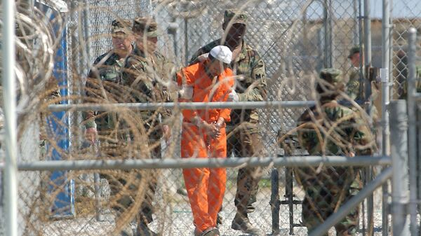 A detainee from Afghanistan is led by military police with his hands chained at Camp X-Ray at the U.S. Naval Base in Guantanamo Bay, Cuba, in this Feb. 2, 2002, file photo - Sputnik International
