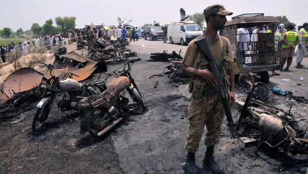A soldier stands guard amid burnt out cars and motorcycles at the scene of an oil tanker explosion in Bahawalpur, Pakistan - Sputnik International