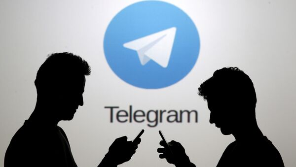 Men pose with smartphones in front of a screen showing the Telegram logo in this picture illustration November 18, 2015. - Sputnik International