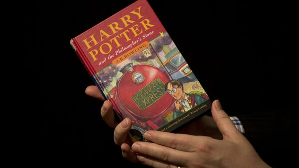 Sotheby's director of the department of printed books and manuscripts Dr Philip Errington poses for photographers with a first edition copy of the first Harry Potter book Harry Potter and the Philosopher's Stone containing annotations and illustrations by author J.K. Rowling, during a photocall organized for the media at the auction house's premises in London. (File) - Sputnik International