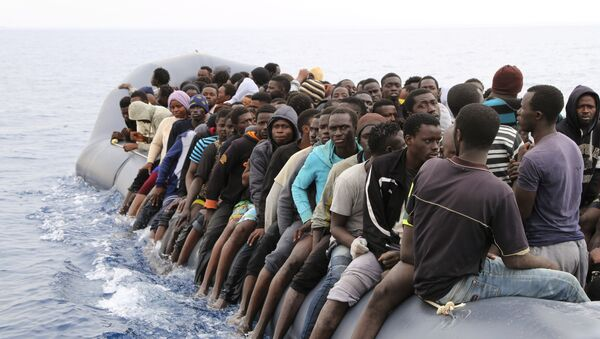 Migrants wait to be rescued from a sinking dingey off the Libyan coasal town of Zawiyah, east of the capital, on March 20, 2017, as they attempted to cross from the Mediterranean to Europe. - Sputnik International