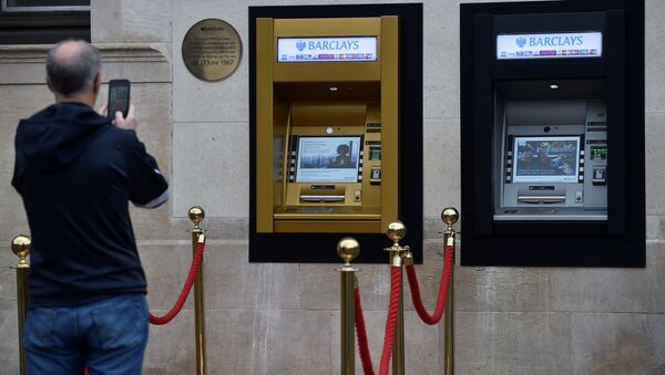 A man photographs a golden ATM, marking the location of the first 'hole in the wall,' which opened fifty years ago, in Enfield, Britain June 27, 2017. - Sputnik International