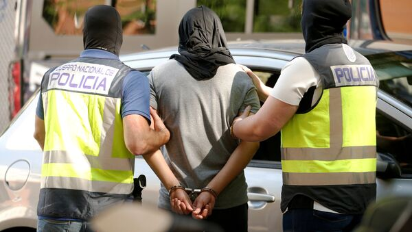 Police lead away a suspect from an apartment block during a raid in which they arrested a 32-year-old Moroccan they said was highly radicalised, in Madrid, Spain June 21, 2017 - Sputnik International