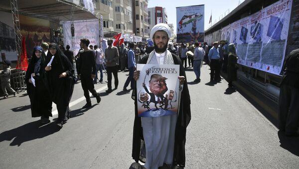 A clergyman holds a poster showing caricatures of U.S. President Donald Trump, center, Israeli Prime Minister Benjamin Netanyahu, left, and Saudi Arabia's King Salman in an annual pro-Palestinian rally marking Al-Quds (Jerusalem) Day in Tehran, Iran, Friday, June 23, 2017 - Sputnik International