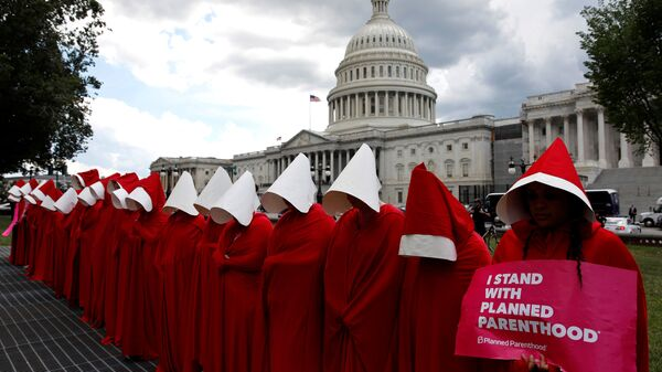 Women dressed as handmaids from the novel, film and television series The Handmaid's Tale demonstrate against cuts for Planned Parenthood in the Republican Senate healthcare bill at the U.S. Capitol in Washington, U.S., June 27, 2017 - Sputnik International