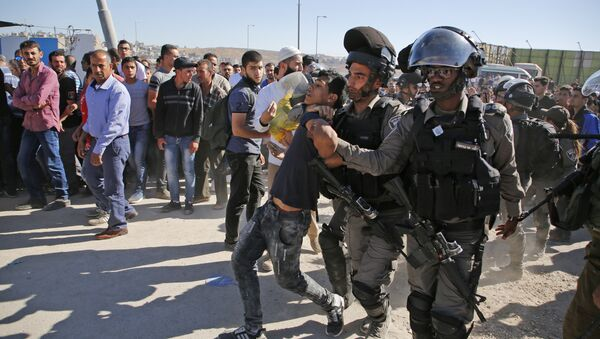Israeli border police detain a Palestinian youth as crowds make their way through the Israeli Qalandia checkpoint, in the occupied West Bank between Ramallah and Jerusalem, to attend Friday prayer of the holy fasting month of Ramadan in Jerusalem's al-Aqsa mosque, on June 16, 2017 - Sputnik International