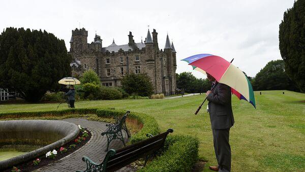 A journalist waits in the rain outside Stormont Castle in Belfast, Northern Ireland June 29, 2017. - Sputnik International