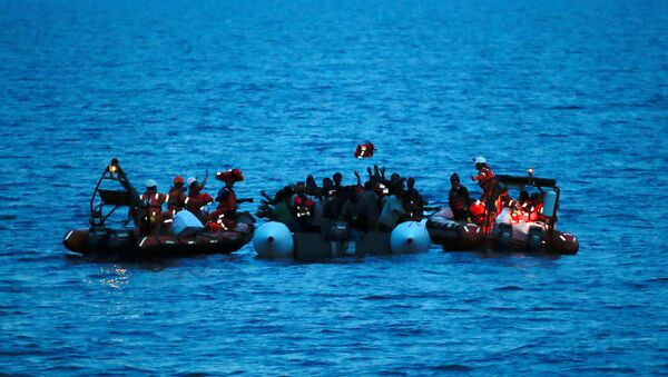 Migrants on a dinghy are rescued by Save the Children NGO crew from the ship Vos Hestia in the Mediterranean sea off Libya coast, June 17, 2017 - Sputnik International