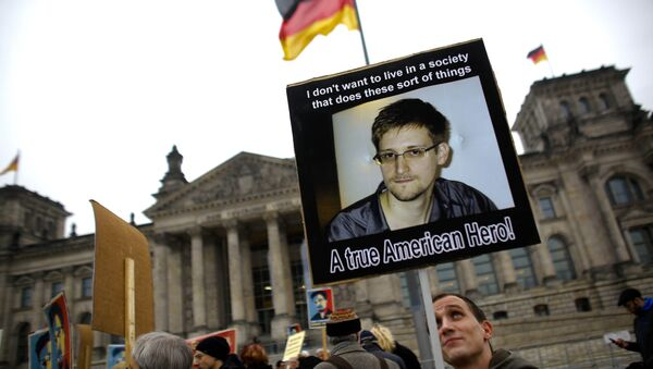 Protesters hold posters of former National Security Agency member Edward Snowden in front of the German parliament building, the Reichstag, prior to a special meeting of the parliament on US-German relationships, in Berlin, Monday, Nov. 18, 2013 - Sputnik International
