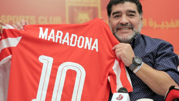 Former Argentinian footballer and manager Diego Armando Maradona holds a jersey of the football club Fujairah FC, bearing his name on the reverse, during a press conference where he was announced as the upcoming manager for the team, in the Gulf emirate of Fujairah on May 14, 2017 - Sputnik International
