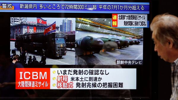 A man walks past a street monitor showing news of North Korea firing a ballistic missile in Tokyo, Japan, July 4, 2017. - Sputnik International