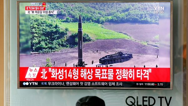 A man watches a TV broadcasting still photographs released by North Korea's state-run television KRT of North Korea's Hwasong-14 missile, a new intercontinental ballistic missile, which they said was successfully tested, at a railway station in Seoul, South Korea, July 4, 2017. - Sputnik International