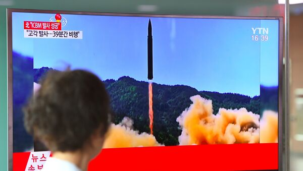 A woman walks past a television screen showing a picture of North Korea's launch of an intercontinental ballistic missile (ICBM), at a railway station in Seoul on July 4, 2017. - Sputnik International