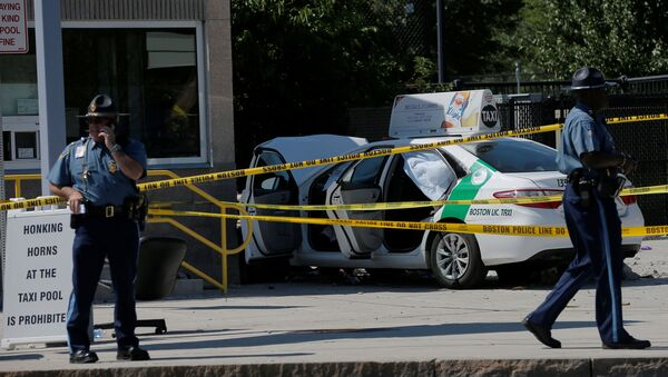 A Massachusetts State Police officer walks past the scene where a taxi cab crashed into a group of bystanders at the taxi pool at Logan International Airport in Boston, Massachusetts, U.S - Sputnik International